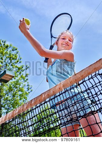 Girl holding  racket and ball on  brown tennis court.
