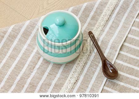 Green pastel porcelain jar and brown spoon with cute fabric.