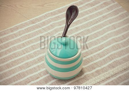 Green pastel porcelain jar and brown spoon in vintage style.