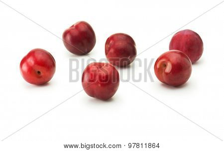 Fresh harvested red ripe plums, isolated on white. Five shiny red plums on white surface.