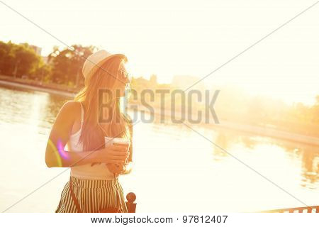 Portrait of a girl in a hat walking in a city park with a paper cu of coffee . Shooting at sunset.