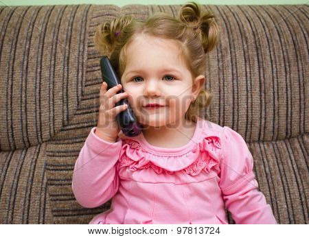 Portrait Of A Cute Little Girl On Chair Talking On The Phone.
