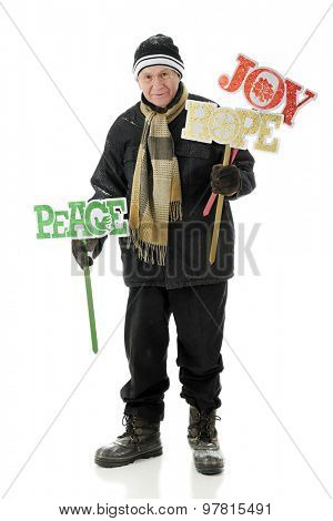 A bundled senior man happily preparing to place cheerful yard signs for Christmas.  On a white background.