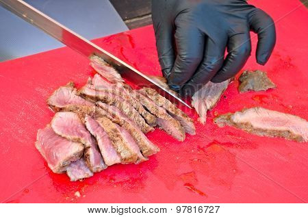 Slicing grilled meat medium rare