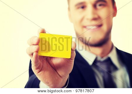 Handsome businessman showing his yellow personal card.