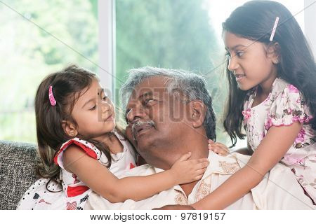 Happy Indian family at home. Asian grandfather and granddaughters having sweet conversation. Grandparent and grandchildren indoor lifestyle.