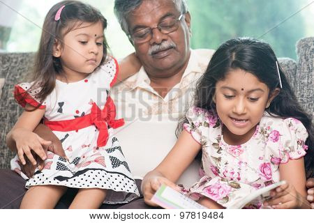 Happy Indian family at home. Asian grandfather and granddaughters reading story book. Grandparent and grandchildren indoor lifestyle.