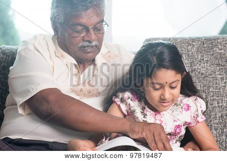 Grandparent and grandchild reading story book together. Happy Indian family at home. Asian grandfather and granddaughter indoor lifestyle.