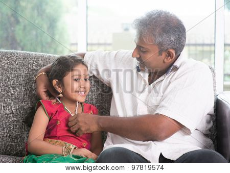 Indian father dressing daughter at home, preparing for diwali. Asian family indoors living lifestyle.