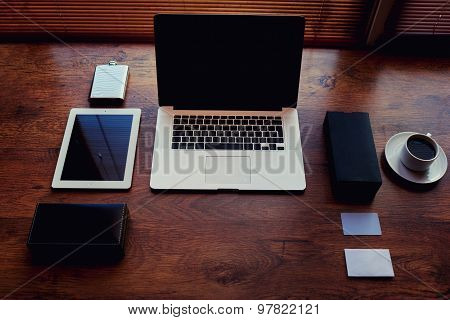 Modern devices with blank screen and accessories lying on the wooden table