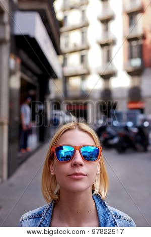 Cute hipster girl in summer sunglases looking to the camera with copy space above her head