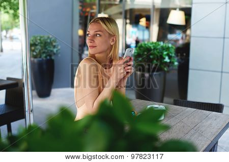Portrait of young businesswoman using smart phone in sidewalk cafe while waiting for a meeting