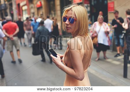 Charming young female in summer dress and sunglases walking down street with smart phone