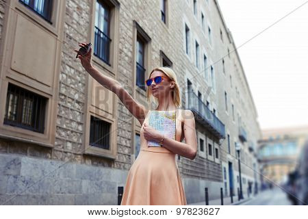 Gorgeous young woman making self portrait with a cell phone camera while enjoying a beautiful day