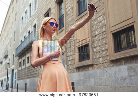 Stylish female hipster taking a picture of herself on smart phone while strolling in new city