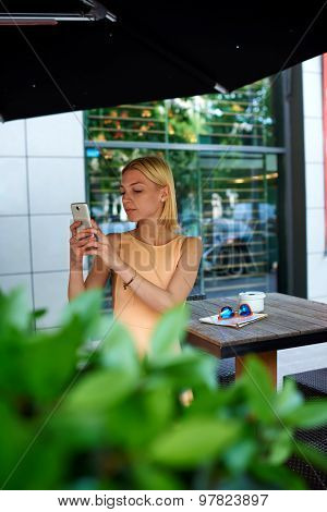 Charming woman in dress photographing urban view with mobile phone camera during summer journey