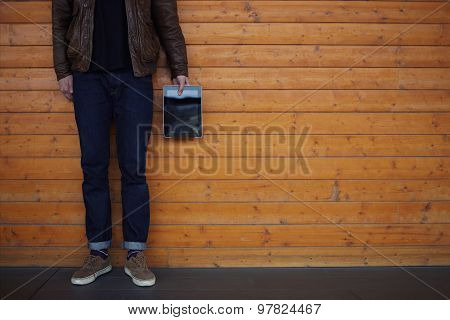 Cropped image with young male hipster hand holding touch pad while standing on wooden background