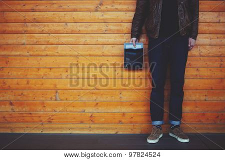 Cropped image with stylish man holding blank digital tablet while standing on wooden background