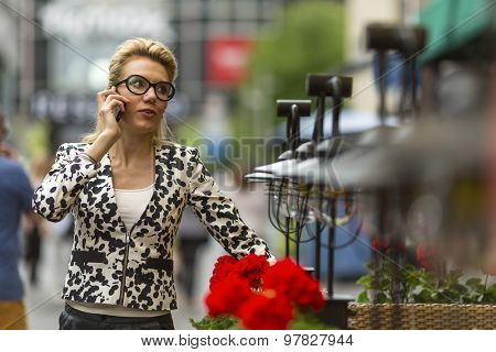Stunning young woman talking on the phone standing on the street.