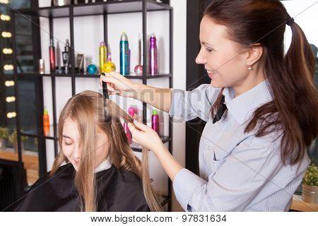 Stylist make curls hair in salon