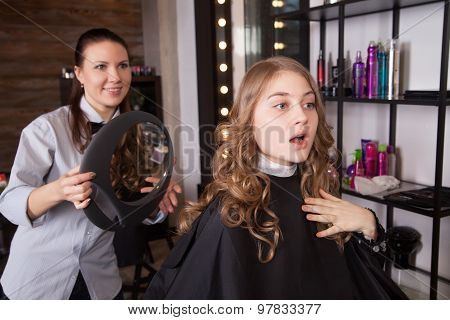 Happy and surprised client looking at mirror in salon
