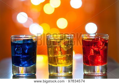 Three glasses with berry liqueur on the bar at a nightclub