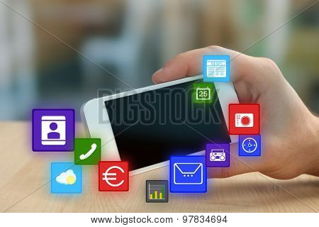 Smart-phone in hand and icons around on blurred color background