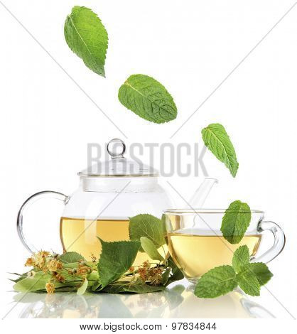 Kettle and cup of tea with linden and falling mint leaves isolated on white
