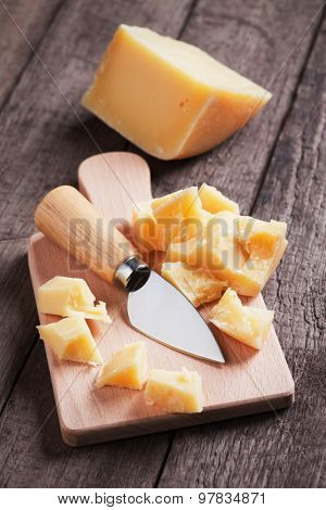Hard, ripened parmesan or grana padano cheese on wooden board