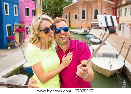 Cheerful couple taking selfie photo with smartphone