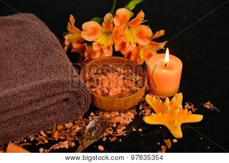 Spa and wellness setting with natural bath salt, candles and towel,orchid