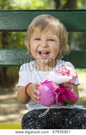 Adorable One Year Old Baby Girl Sitting On A Bench With A Doll In Her Hands
