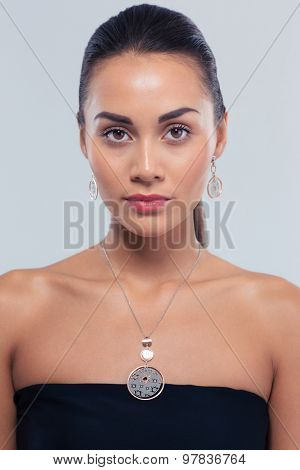 Jewerly concept. Portrait of a charming fashion woman on gray background. Looking at camera
