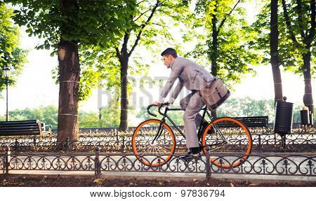 Businessman riding bicycle to work in park