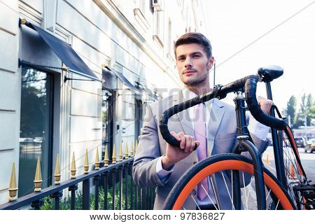 Confident businessman carrying his bicycle on city streets