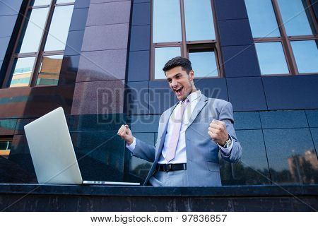 Happy businessman looking at laptop and celebrating his success outdoors