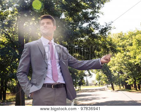 Businessman stopping car with hand outdoors