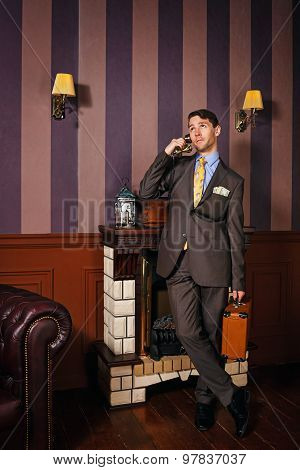 Businessman Speaks By Phone, Holding A Suitcase.