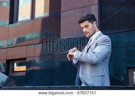 Businessman looking on wrist watch outdoors near office building