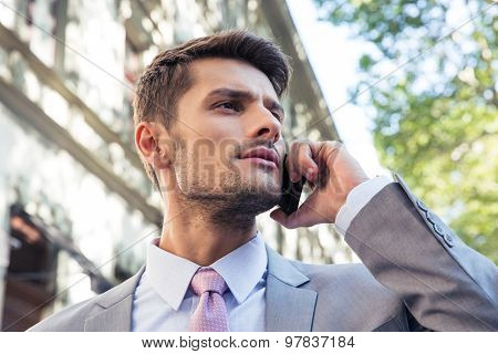 Thoughtful businessman talking on the phone outdoors