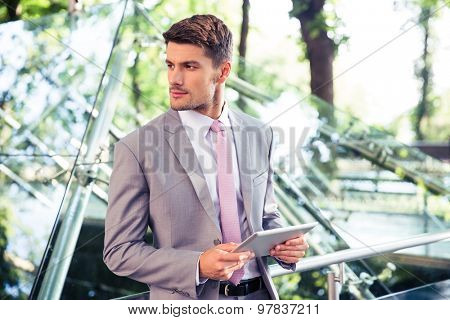 Pensive businessman standing with tablet computer near glass building