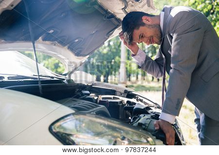 Man in suit looking under the hood of breakdown car outdoors