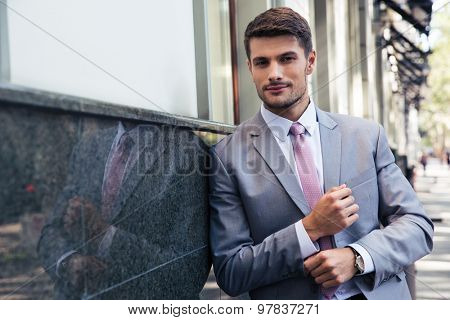 Confident businessman standing outdoors and looking at camera