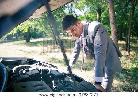 Man in suit looking under the hood of breakdown car