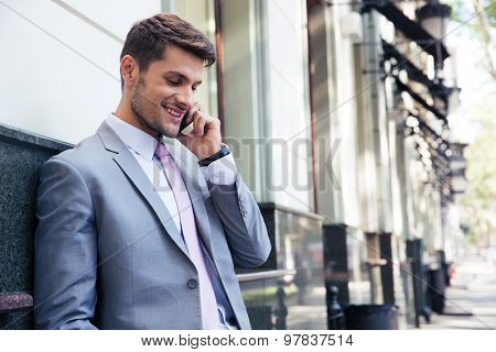 Smiling businessman talking on the phone outdoors