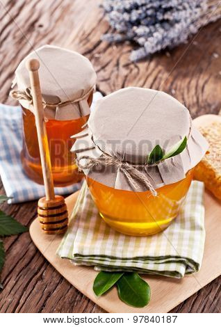 Glass cans full of honey on old wooden table.