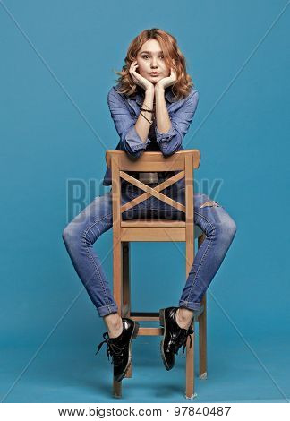 Dreaming Girl Sits On A Chair On A Blue Background