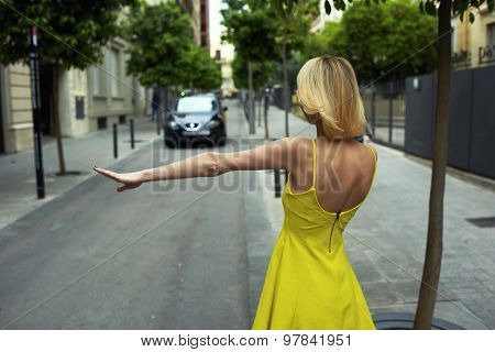 Back view young female tourist with hand gesture stopping taxi in urban setting