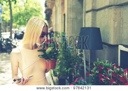 Young attractive woman smelling flowers while shopping plants in urban sidewalk botany shop