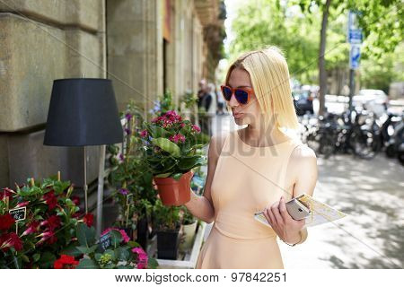 Attractive female holding city map smartphone and flower pot for buy at urban sidewalk botany shop